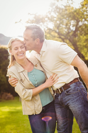 cheek: Husband kissing wife on the cheek outside