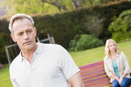 sulking: Couple sulking each other in the garden Stock Photo