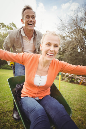 Husband pushing wife in a wheelbarrow in the garden