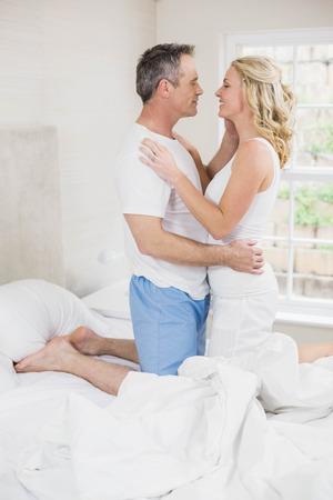 pareja en la cama: linda pareja a punto de besar en su habitación