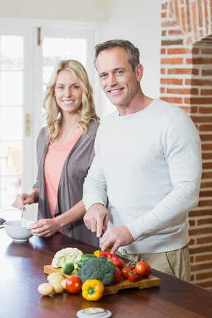 middleaged: Cute couple slicing vegetables in the kitchen Stock Photo