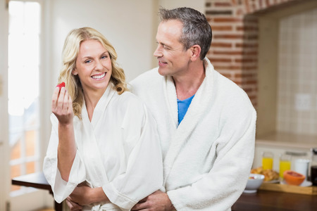 bathrobes: Cute couple cuddling in bathrobes in the kitchen Stock Photo