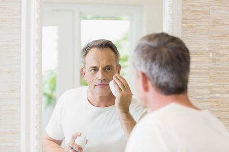 cocooning: Handsome man applying shaving foam in the bathroom Stock Photo
