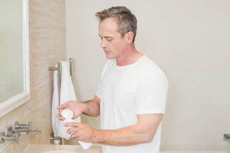 Handsome man applying cream in the bathroom Stock Photo