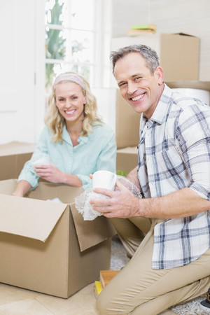sealing tape: Smiling couple packing mug in a box at home
