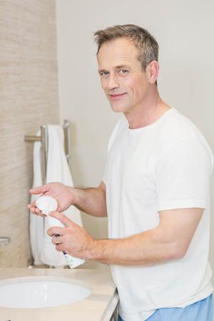 cocooning: Handsome man applying cream in the bathroom Stock Photo