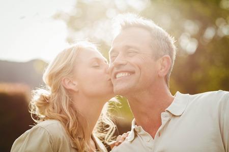 pareja besandose: Esposa besando marido en la mejilla fuera