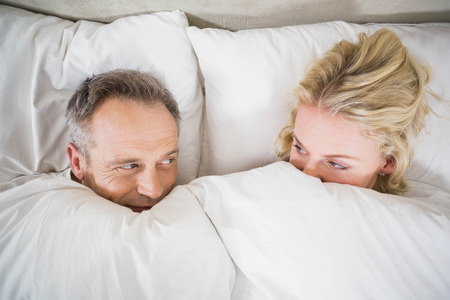 cuddling: Cute couple cuddling in bed in their room Stock Photo