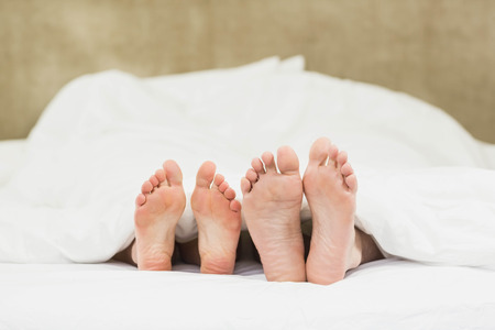 bed feet: Close up of couples feet in their bed