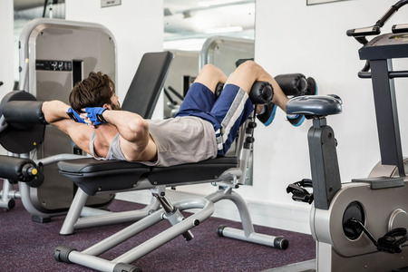 crunches: Man doing abdominal crunches on bench at the gym