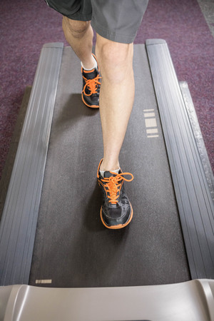 lower section: Lower section of man running on treadmill at the gym Stock Photo