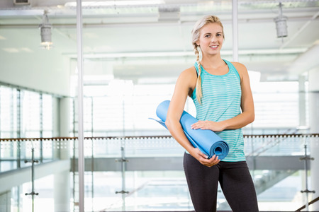 leisure centre: Smiling blonde holding yoga mat at leisure centre Stock Photo