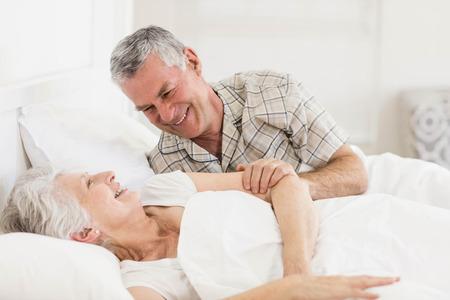 waking up: Happy senior couple at bed at home