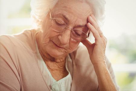 dolor de cabeza: mujer de edad avanzada con dolor de cabeza en el hogar