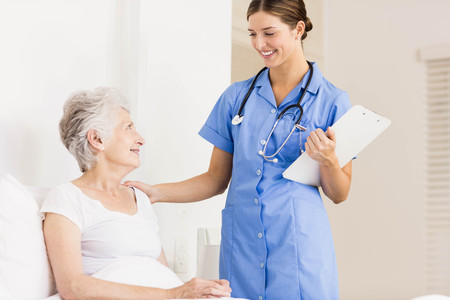 seniors suffering painful illness: Doctor taking care of suffering senior patient at home Stock Photo
