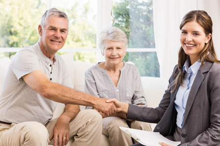 Businesswoman and senior man handshaking at home