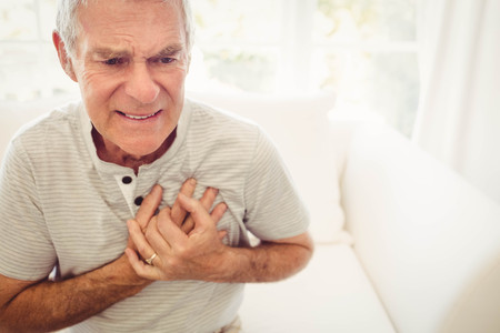 Senior man with pain on heart in bedroom Stockfoto