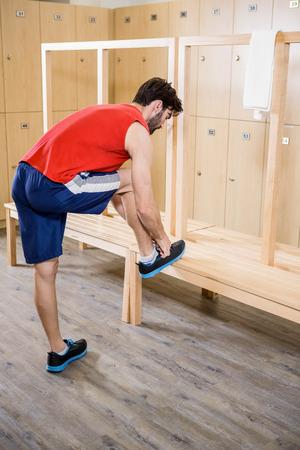 locker room: Man tying shoelace in locker room at the gym