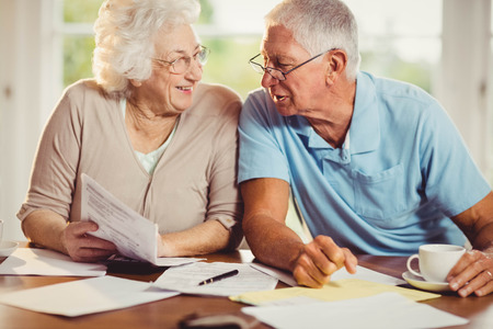 figuring: Senior couple counting bills at home