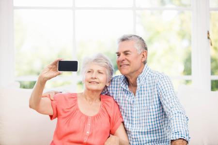 home life: Happy senior couple taking a selfie on the sofa