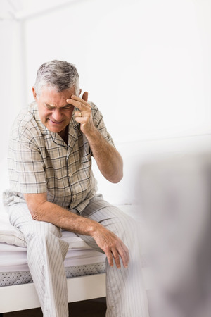 seniors suffering painful illness: Suffering senior man touching his forehead at home