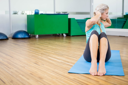 sitting up: Fit blonde doing sitting up on mat in fitness studio Stock Photo