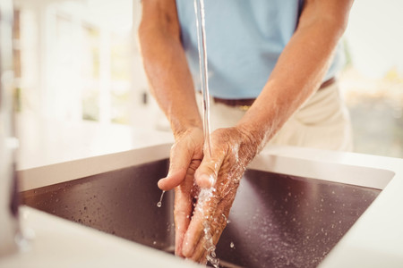mid section: Mid section of senior man washing hands in the kitchen Stock Photo
