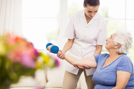 home care: Physiotherapist taking care of sick elderly patient at home