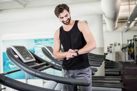 fitness hombres: Hombre sonriente en el tapiz rodante mirando SmartWatch en el gimnasio