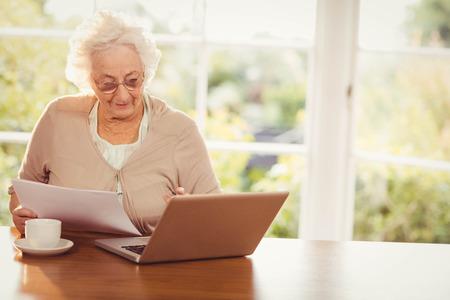Hogere vrouw omgaan met documenten tijdens het gebruik van laptop thuis