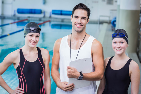 Portrait of smiling trainer and swimmers at the leisure center