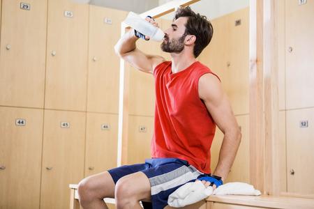 locker room: Handsome man drinking water in locker room Stock Photo