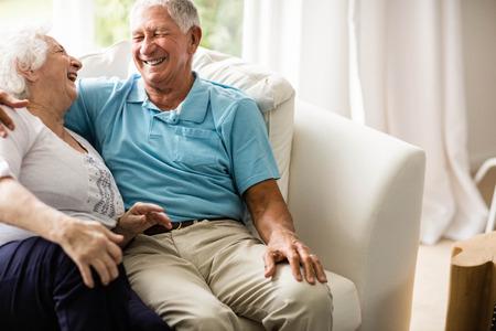 cuddling: Cute senior couple hugging on sofa