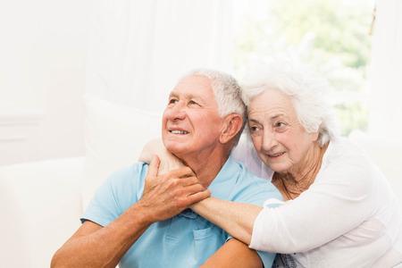 parejas felices: Linda pareja abrazándose mayores en el sofá