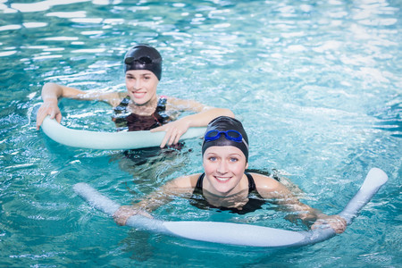 water aerobics: Smiling women in the pool with foam rollers at the leisure center