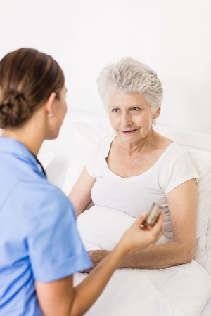 seniors suffering painful illness: Nurse taking care of suffering senior patient at home Stock Photo