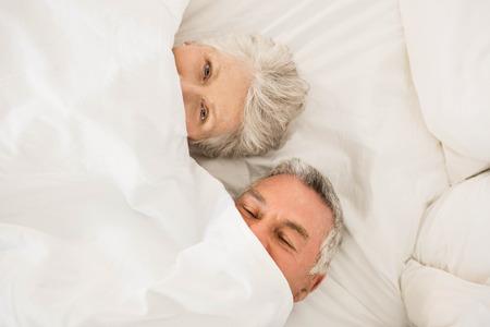 couple bed: Heureux couple de personnes âgées sous une couette dans le lit en regardant la caméra Banque d'images