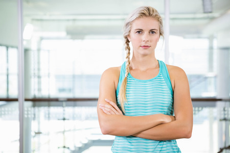 slim women: Serious blonde standing with arms crossed at the leisure center