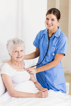 seniors suffering painful illness: A smiling nurse with her patient beside her