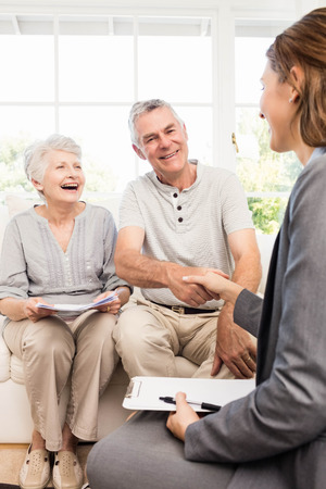 inquiring: Businesswoman talking with senior couple at home Stock Photo