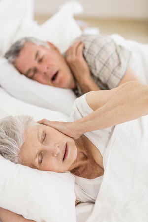 Awake senior woman in bed covering her ears while her husband is snoring Reklamní fotografie - 52344308