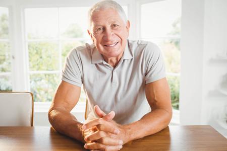 crossing fingers: Happy senior man crossing fingers at home