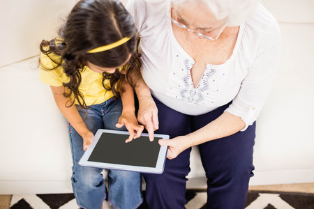 multi family house: Concentrated granddaughter using tablet with grandmother at home