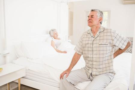 Suffering senior man holding his back at home Reklamní fotografie
