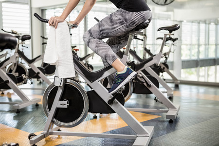 lower section: Lower section of fit woman on exercise bike at the gym