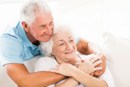 elderly man: Cute senior couple hugging on sofa