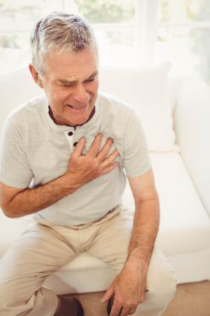corazon en la mano: Hombre mayor con dolor de corazón en el dormitorio
