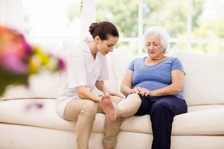 Physiotherapeut kümmert sich um kranken älteren Patienten zu Hause Standard-Bild - 52350197