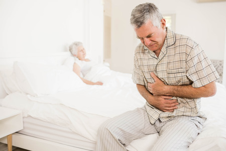seniors suffering painful illness: Suffering senior man holding his belly at home