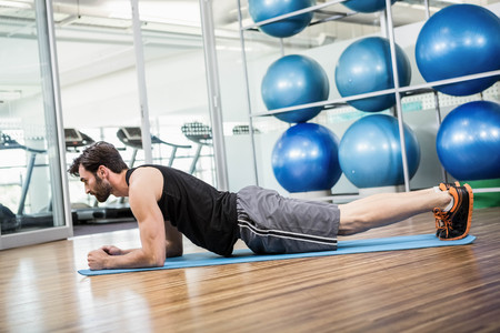 free weight: Serious man doing exercise on the mat in the studio Stock Photo